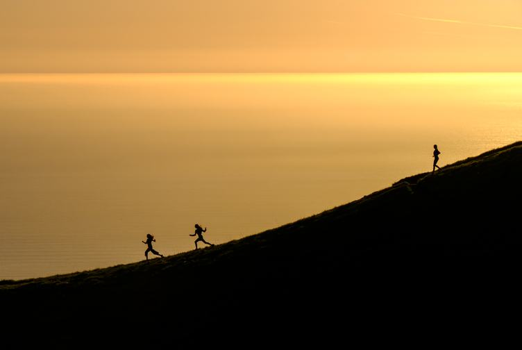 Women Silhouettes Running at Sunset with the Ocean in the Background