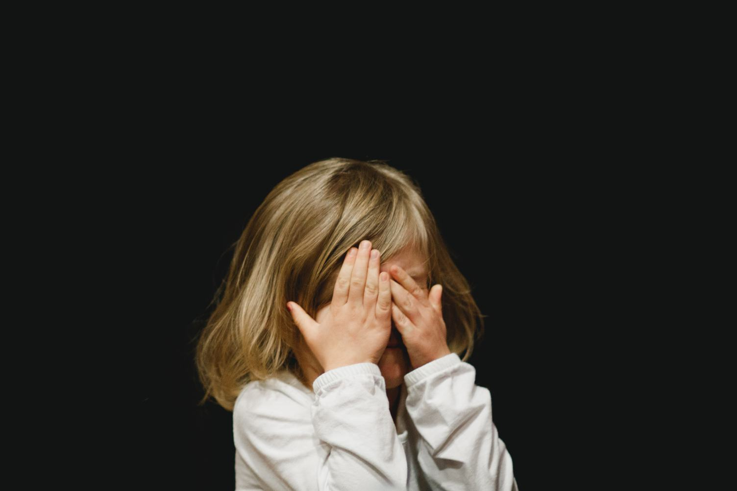 Little Girl Covering Her Face with her Hands on Black Background