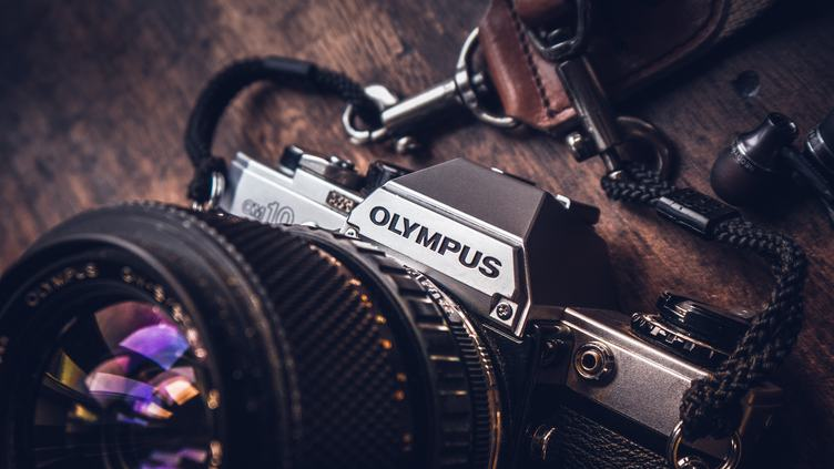 Old SLR Olympus Camera on Wooden Background