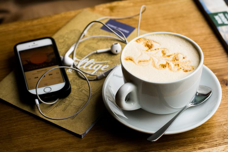 iPhone with the EarPods and Coffee on a Wooden Table