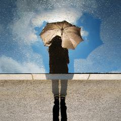 Puddle Reflection Silhouette of Girl with Umbrella against Blue Sky