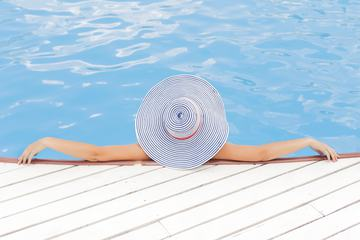 Young Woman Wearing Striped Hat Enjoying a Swimming Pool