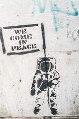 "Dirty Wall with Graffiti Astronaut Holding Flag ""We Came in Peace"""