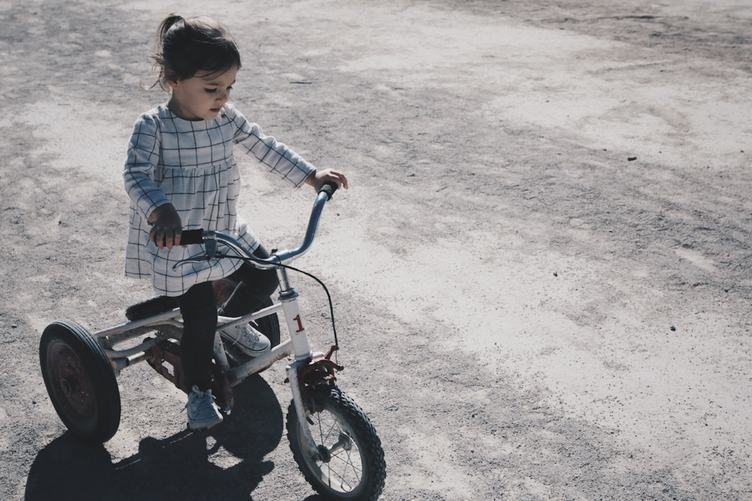 A Little Girl Riding a Tricycle Bike