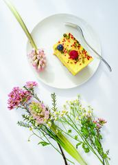 Slice of Cheesecake Decorated with Fruits Surrounded by Flowers on White Table