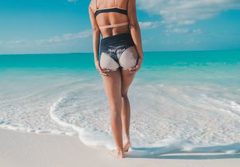 Sexy Woman Buttocks on Azure Sea and Blue Sky