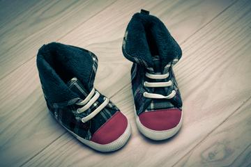 Pair of Cute Baby Sneakers over White Wooden Floor