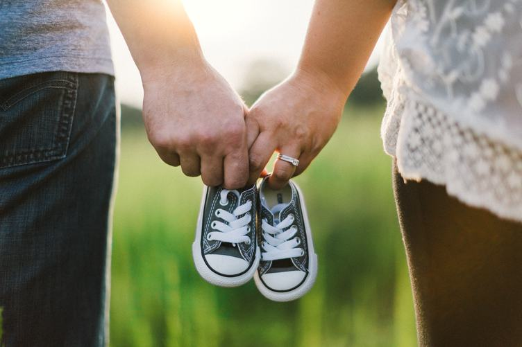 Future Parents Holding Hands and a Pair of Little Baby Shoes