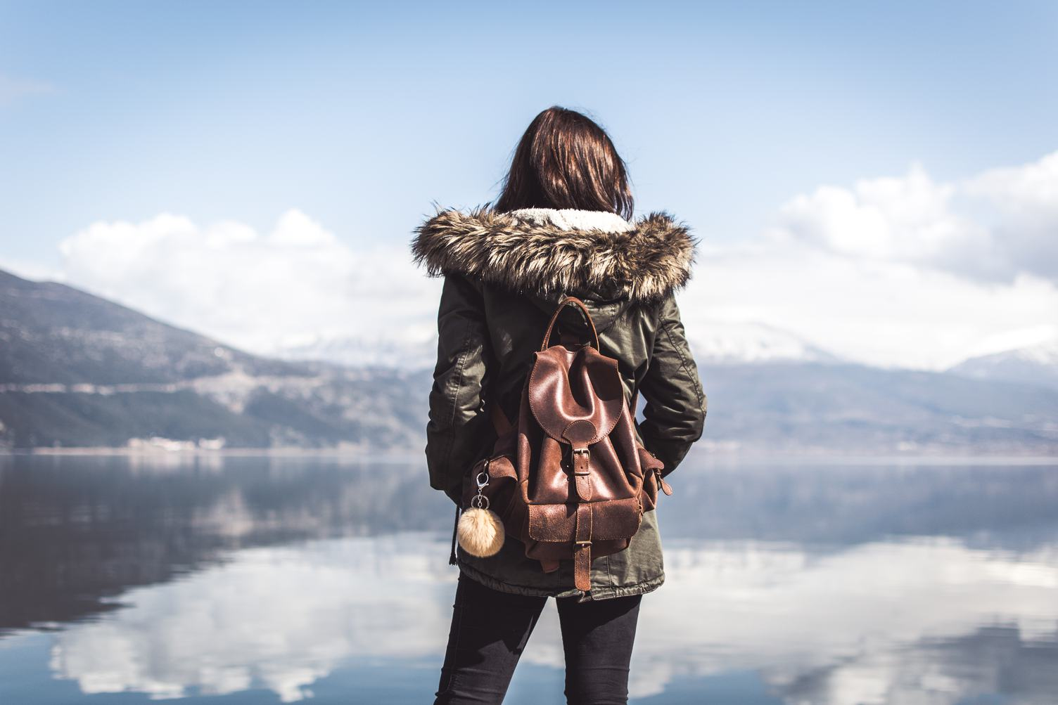 Young Woman with Backpack Looking on the Lake, Rear View