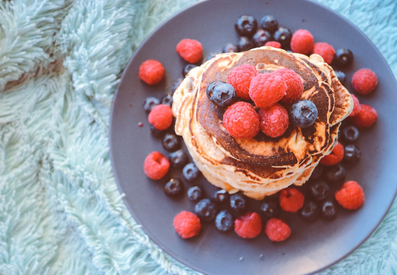 Pancakes with Blueberries and Raspberries on Black Plate