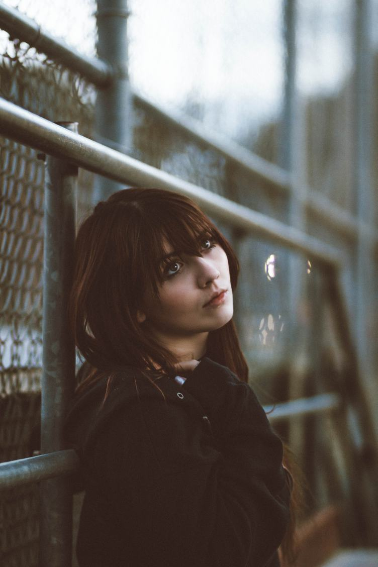Young Woman Lean on Fence