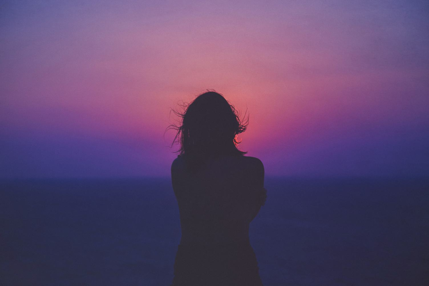 Young Woman Standing against Pink and Purple Sky