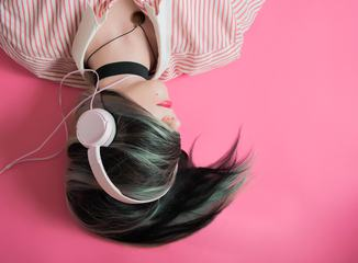 Young Girl Listen to Music Lying on Pink Background