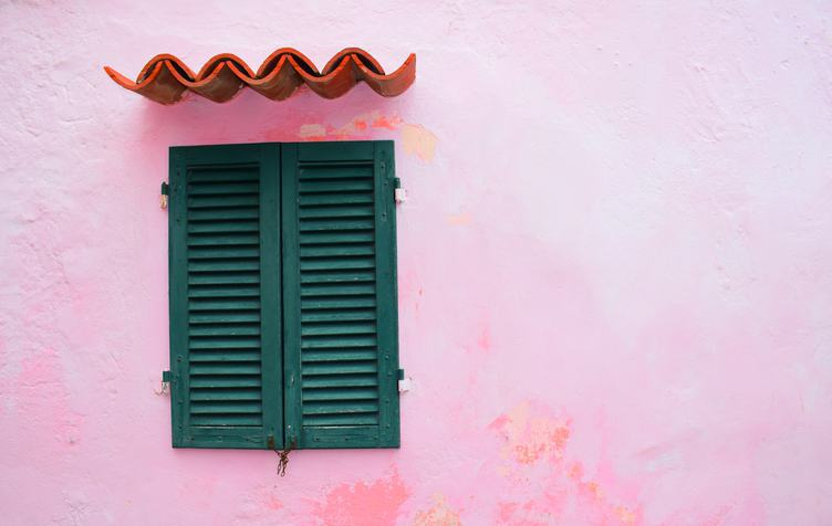 Closed Green Window Shutters on Grunge Pink Wall Background