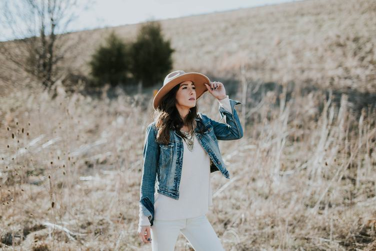 Young Woman in Hat and Denim Jacket Standing Outdoors