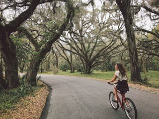 A Young Woman Is Cycling in the Park