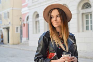 Beautiful Fashionable Woman in a Hat and Black Leather Jacket Holding Coffee