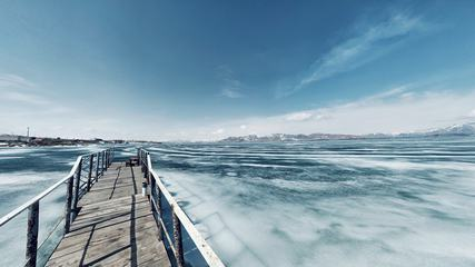 Scenery with a Pier in a Frozen Lake