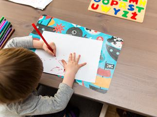 Left-Handed Little Boy Drawing with Red Marker