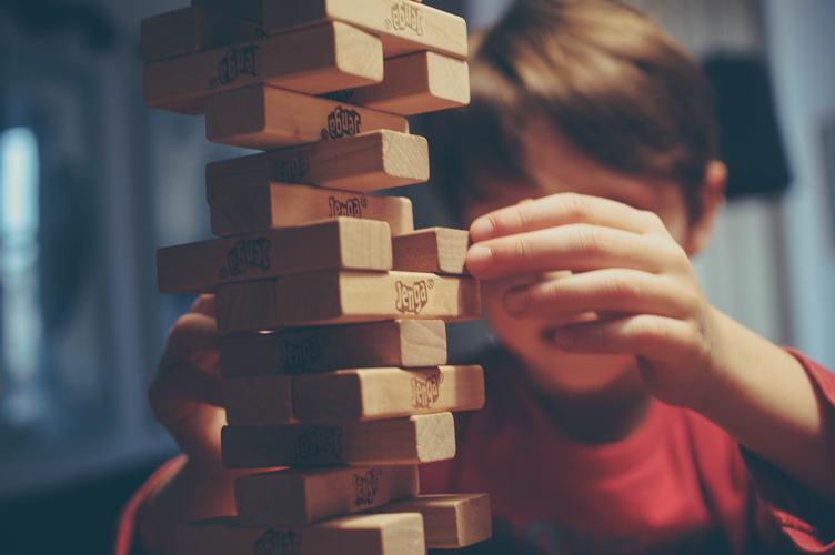 Boy is Playing Jenga, a Wood Blocks Tower Game