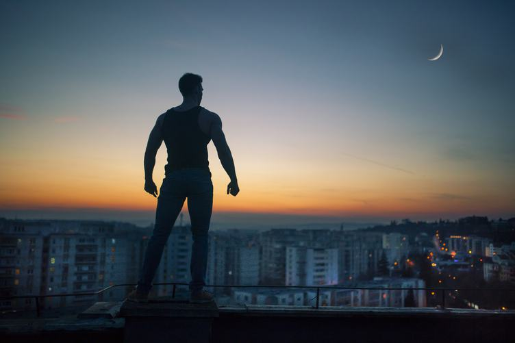 Brave, Young and Muscular Man Standing on the Roof Looking Far Away at Sunset