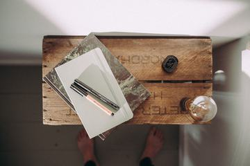 Top View of Notebook with Pen and Light Bulb on Wooden Table