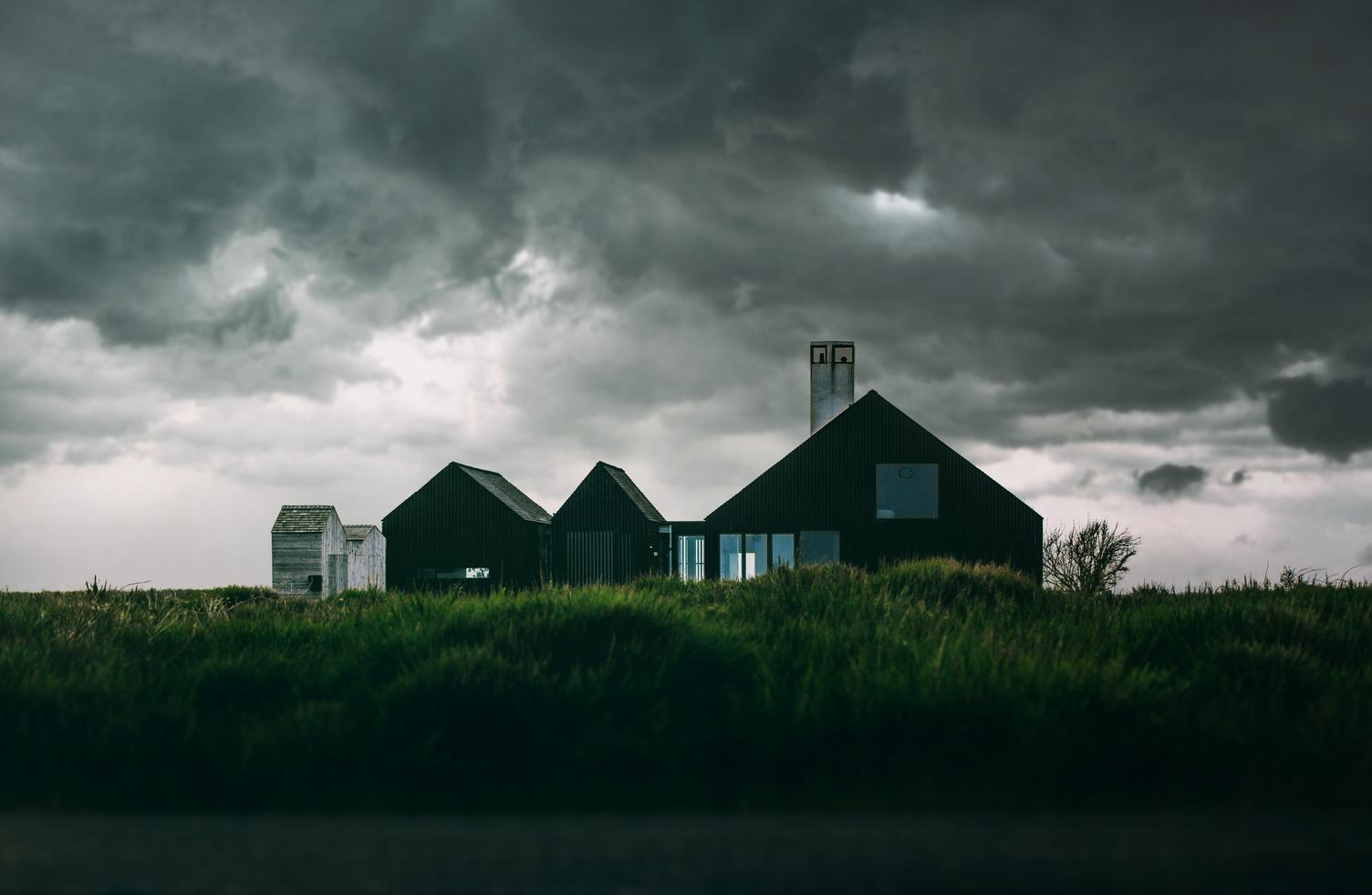 Modern House on the Green Land and Dramatic Clouds