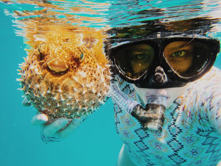 Young Woman Snorkeling in a Tropical Sea and Holding Fish