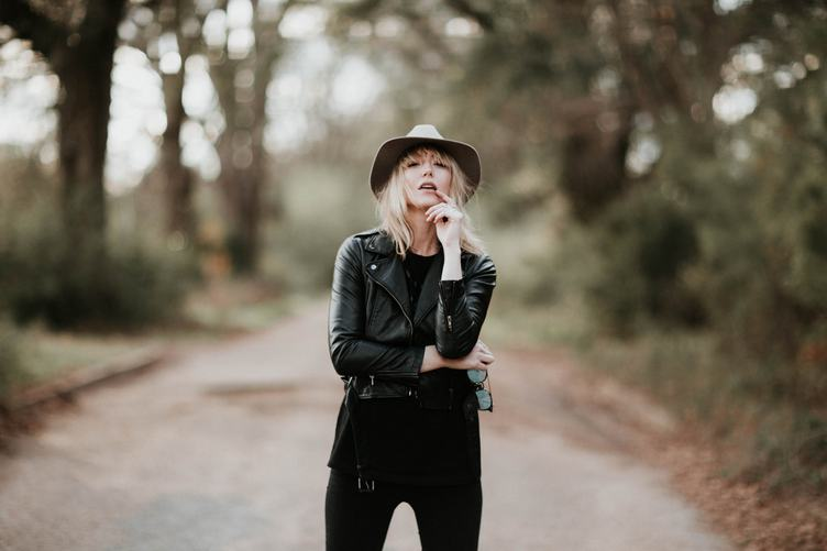Fashion Blonde Woman Posing Outdoor in Black Hat and Leather Jacket