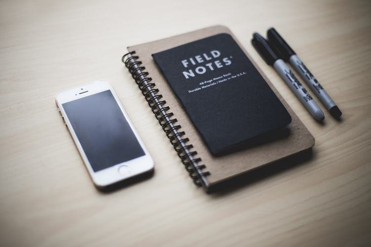 Notepad, iPhone and Pen on Wooden Background