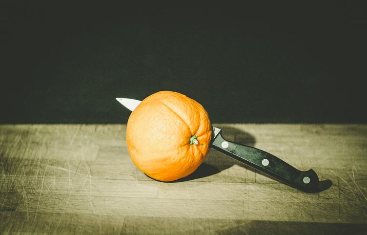 Orange with Knife on Old Cutting Board