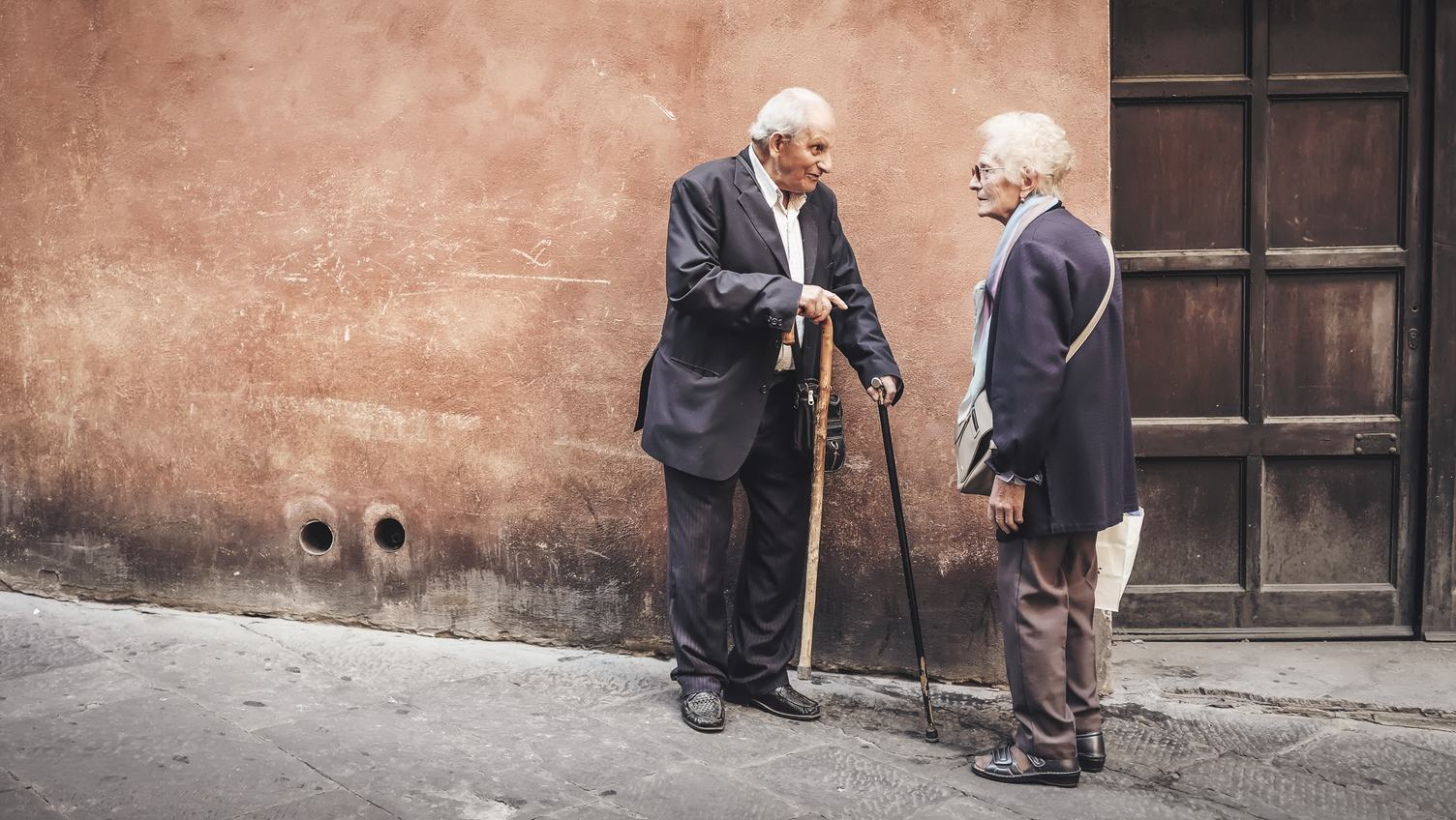 Couple of Senior Friends Standing and Talking on the Sidewalk