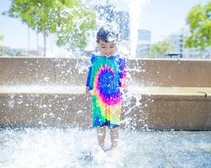 Smiling Boy is Bathed and Splashing in the Fountain
