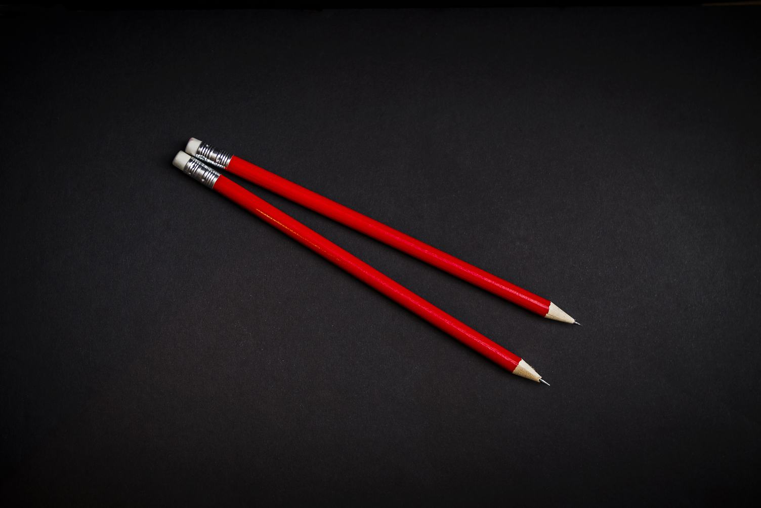 Two Red Pencils on Black Background