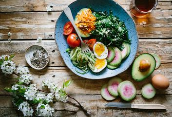 Top View of Healthy Salad Bowl with Eggs, Tomatoes, Avocado and other Vegetables on Wooden Table