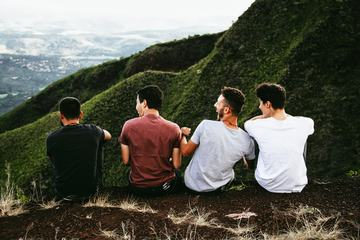 Four Guys Sitting on Cliff and Talking and Laughing