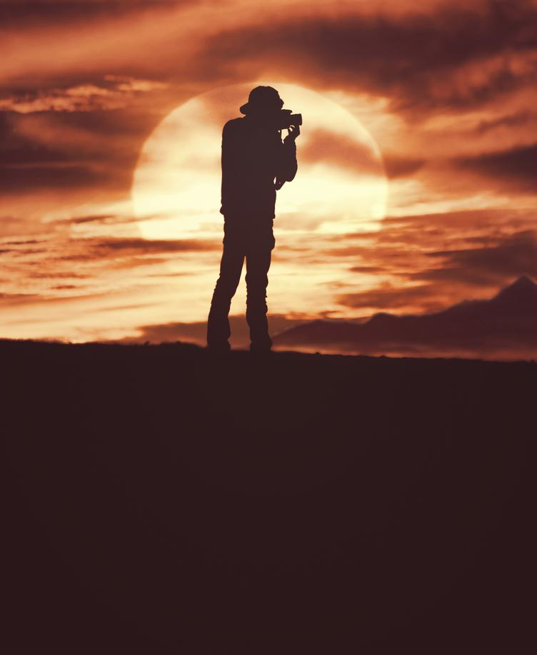 Photographer Silhouette Shooting Outdoors at Sunset Background