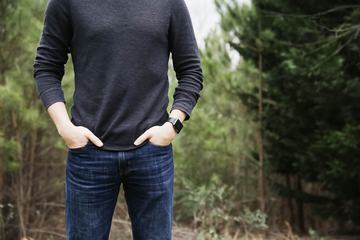 Man Standing in the Forest with Apple Watch on Hand