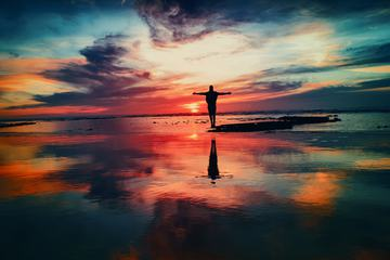 Men with Open Arms Standing in Water Against the Incredible Sunset Sky