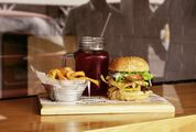 Tasty Burger with Fries and Beverage on Wooden Table
