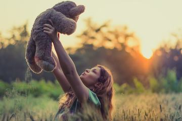 Girl Holding Teddy Bear on the Field at Sunset