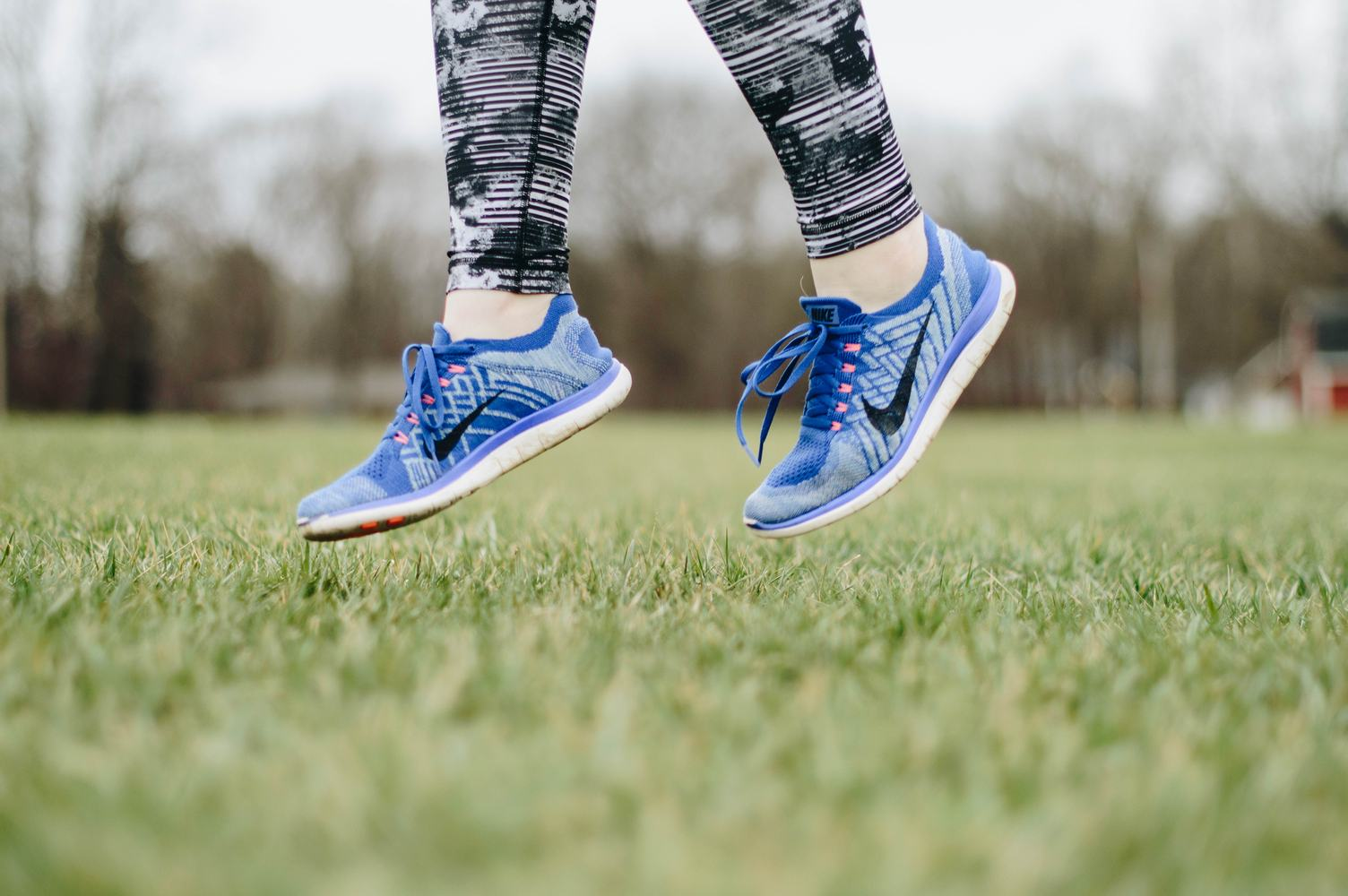 Closeup of Female Legs Wearing Blue Sneakers Jumping on the Grass Outdoors
