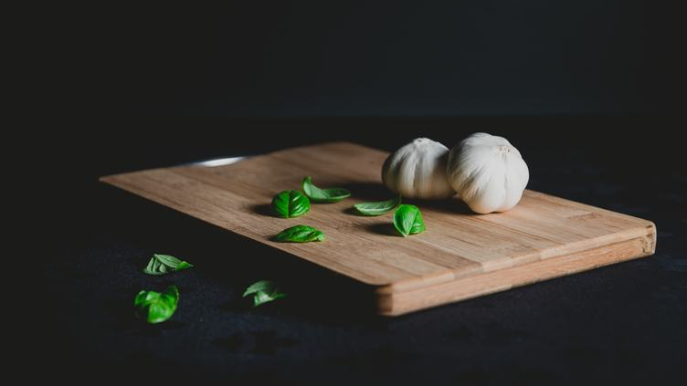 Wooden Chopping Board with Garlic and Basil Leaves on Black Background