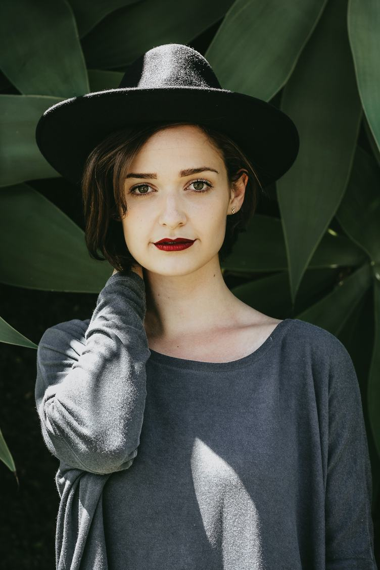 Girl Wearing Black Hat Standing and Looking in the Camera