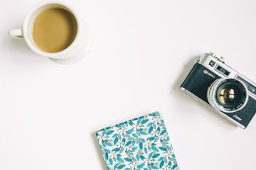 Flat Lay Photography with Camera, Coffee and Notebook on White Background