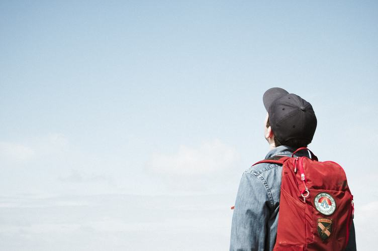 Young Man with Backpack Standing and Looking up at the Sky