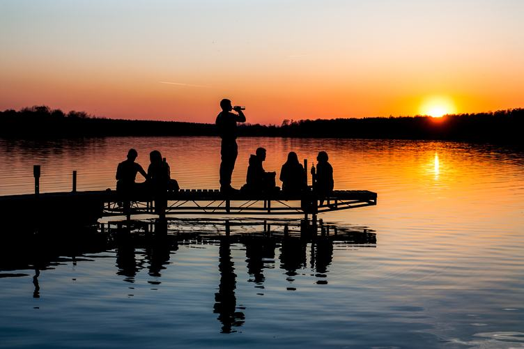 Silhouette of Group of Friends Sitting and Drinking on a Lake Pier at Sunset