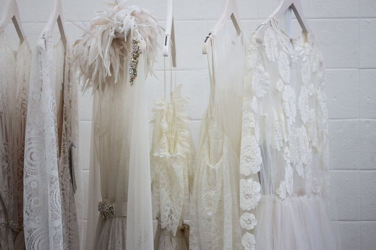 White Elegant Dresses on Hangers against White Wall