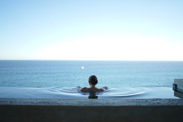 Woman in the Infinity Pool Enjoying the Ocean View