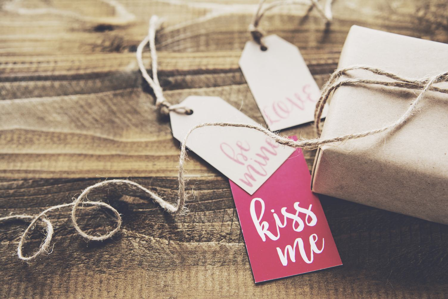 Gift and Labels on Wooden Background
